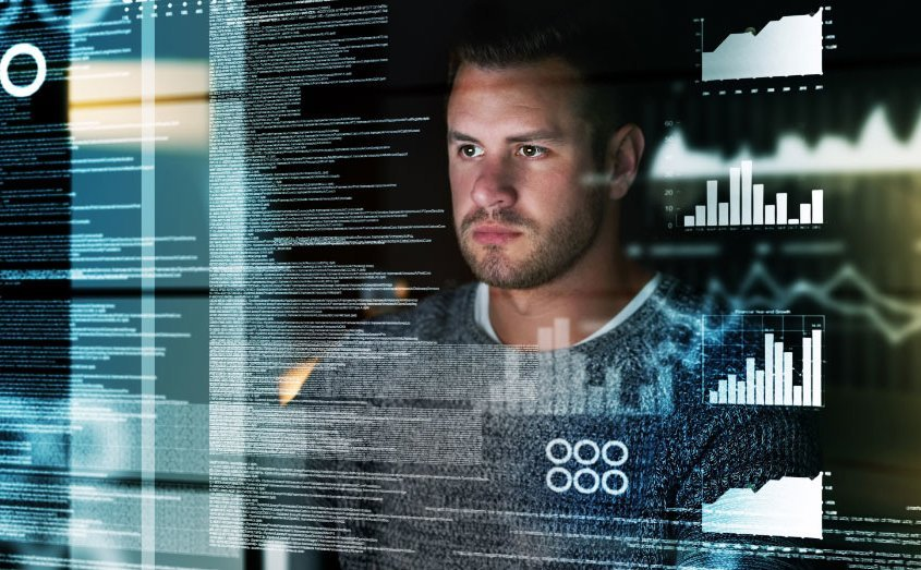 Face of a man looking intently at several layers of translucent text and diagrams
