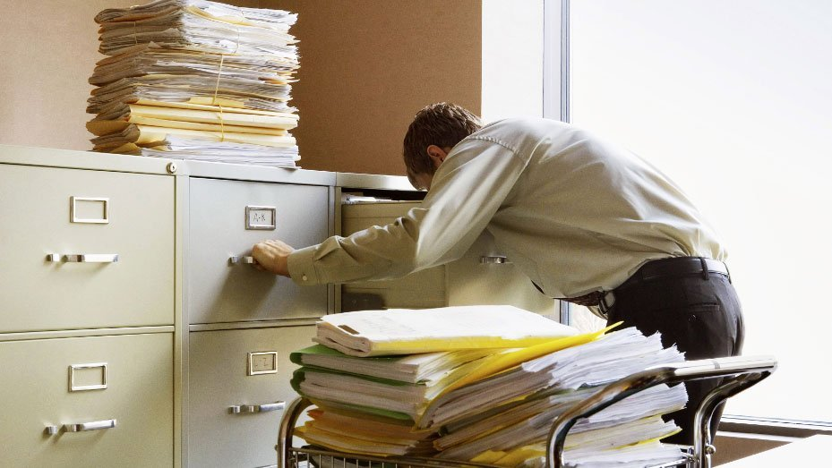 Man surrounded by piles of files searching for documents in filing cabinet