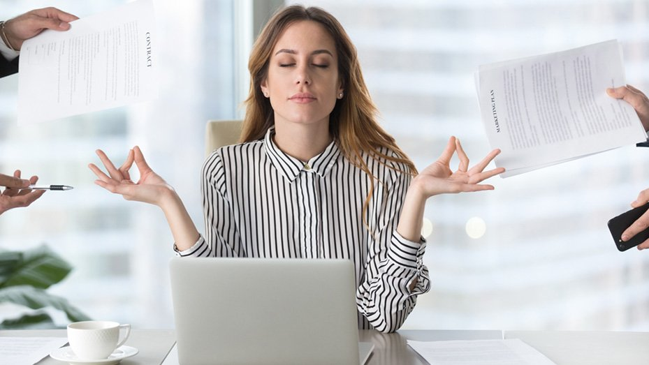 Woman meditating while confronted with several documents