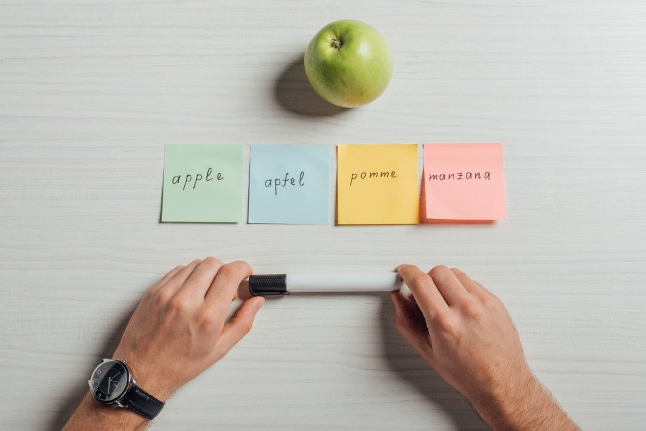 Hands holding a pen, sticky notes with the word apple in multiple languages, and an apple